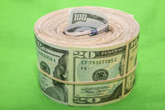 Large paper bill roll rubber band green background Royalty Free Stock Images
