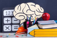 A drawn calculator, a pencil and a brain, next to stationery, books, notebooks and a red juicy apple. Dark background. stock photo