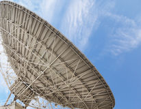 Large satellite antenna soaring into sky Stock Photography