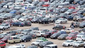 Large parking lot near the shopping center, a lot of cars and hurrying people. Buyers stock video footage