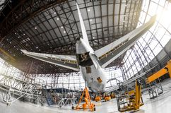 Large passenger aircraft on service in an aviation hangar rear view of the tail, on the auxiliary power unitand tail altitude cont. Rol, elevating rudder royalty free stock image