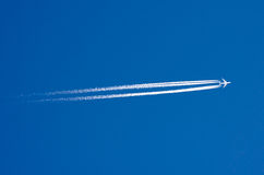 Large passenger liner and trail from an airplane in a blue sky. Stock Images