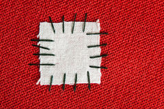 Large patch on red cloth Stock Images