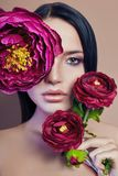 Large peonies near a woman face, art fashion flowers in front of a girl, nature face care, natural cosmetics