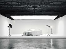 Large photographic studio with a car and several light sources. 3d rendering Stock Image