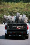 Truck carry big rig semi trucks old used tires on the road. A large pickup truck transport used tires with large tread pattern for big rig semi trucks in its royalty free stock photos