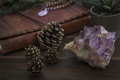 Large Piece of Amethyst Crystal with Notebook Plants and Pine Cones on a Wooden Surface. Large piece of amethyst crystal with leatherbound notebook plants and royalty free stock photos