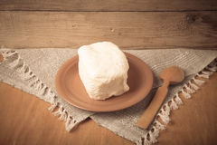 Large piece of butter with spoon on plate on linen napkin. Rusti Stock Image