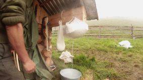Large piece of cheese hanging in cheesecloth for dehydration mountain tradition stock video footage