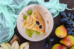 A large piece of a pie with pears and grapes on a plate. On a dark wooden background Stock Photo