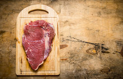 A large piece of raw fresh meat on cutting Board. On a wooden table. Free space for text . Top view Stock Photos