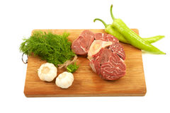 A large piece of red meat, dill, garlic and green pepper on a wo. Oden board on a white background Royalty Free Stock Image