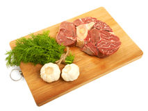 A large piece of red meat, dill and garlic on a wooden board on. A white background Royalty Free Stock Image
