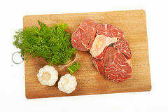 A large piece of red meat, dill and garlic on a wooden board on. A white background Stock Photos
