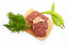 A large piece of red meat, dill and green peppers on a wooden bo. Ard on a white background Royalty Free Stock Photos