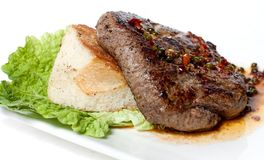 Large piece of roasted meat with sauce. White bread and green salad Stock Image