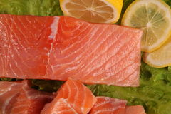 Large piece of salmon with lemon. And green salad Stock Images