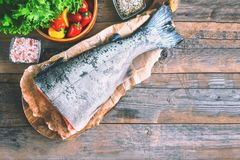A large piece of salmon lying on a wooden table for cooking. Food anti-aging body. Copy the space. The horizontal frame Stock Image