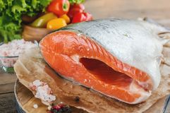 A large piece of salmon lying on a wooden table for cooking. Food anti-aging body. Copy the space. The horizontal frame Stock Images