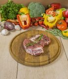 A large piece of steak on a wooden board, against a background of vegetables and greens, a multicolored composition Royalty Free Stock Images