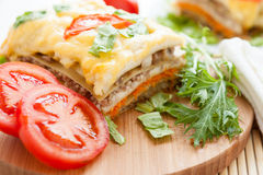 Large piece of vegetable lasagna on a wooden surface royalty free stock photos