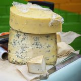 Large pieces of cheese with blue mold on market counter. Gastronomic dainty products on market counter, real scene in. Food market, square background stock photo