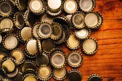 Large pile of beer bottle caps on wooden desk Stock Image