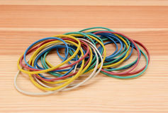 Large pile of coloured rubber bands. Large pile of coloured elastic bands on a wooden background stock image