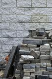 A large pile of disassembled paving tiles against the wall of light brick. S Royalty Free Stock Images