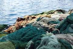 Fishnets by the Water. A large pile of fishnets, out of duty, resting on a commercial dock in the sunlight. Blurred harbor water ripples in the background Stock Photos