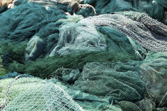 Fishnets at Ease. A large pile of fishnets, out of duty, resting on shore in the sunlight Royalty Free Stock Images