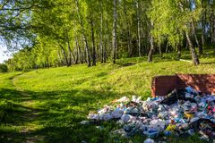 A large pile of garbage in the background of a beautiful landscape royalty free stock photography