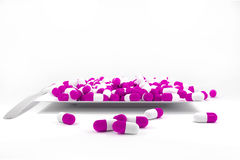 Large pile of purple colored pills on white plate. Silver spoon Stock Images