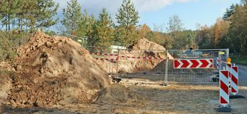 A large pile of sand and steel fence with road sign in a autumn. Forest construction site. Panoramic collage from several outdoor sunny October day shots royalty free stock photos