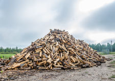 A large pile of split firewood. Large pile of split wood on the background of smooth white-blue sky stock image