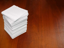 A large Pile of square white sheets lies on a brown table. The photo of the stack of paper can be used as a background Stock Images