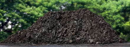 A large pile of thick, Wet black soil mountain shape, Clay pile isolated tree nature Background, Agricultural land for cultivation. Large pile of thick, Wet Stock Photo