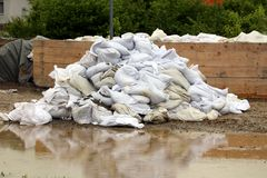 Large pile of white sandbags used for flood protection waiting to be removed after flood surrounded with muddy water and wooden. Boards holding flood protection royalty free stock photos