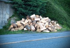 A large pile of wood that has been cut and split into firewood to be used as fuel for heating in fireplaces and furnaces in the stock photo