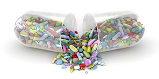 Large pill emptying a pile of colorful pills stock image