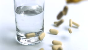 Large pills being poured out beside glass of water stock footage