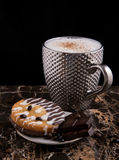 Large pimpled silver cup of coffee and cakes bisquits chocolate and coffee beans on the granite surface and black Stock Image