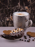Large pimpled silver cup of coffee and cakes bisquits chocolate and coffee beans on the white reflective surface Stock Images