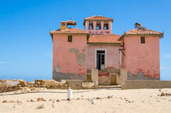 Large pink ruined mansion from Portuguese colonial times in Angola. Large pink ruined mansion from Portuguese colonial times in small coastal village of Angola`s Royalty Free Stock Photos