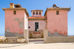Large pink ruined mansion from Portuguese colonial times in Angola. Large pink ruined mansion from Portuguese colonial times in small coastal village of Angola`s Royalty Free Stock Photo