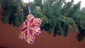 Large pink snowflake with colorful sequins hanging on garland decorating house. Stock footage stock video