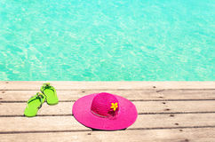 Large pink sun hat and green flip plops on the deck by the sea.  Royalty Free Stock Photography