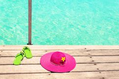 Large pink sun hat and green sandals on the deck by the sea.  Stock Photo