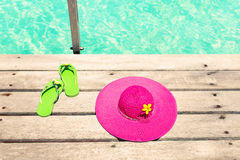 Large pink sun hat and sandal on the deck by the sea Stock Photography