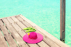 Large pink sun hat and sandal on the deck by the sea Royalty Free Stock Photography